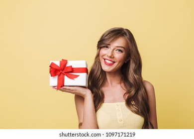 Photo of fascinating woman 20s having long brown hair smiling and holding present box wrapped with bow at her palm isolated over yellow background
