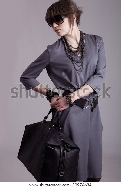 Photo of fashion model with a bag on grey background