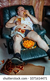 Photo of a fat couch potato eating a huge hamburger and watching television.  Harsh lighting from the television illuminates the dark room.
