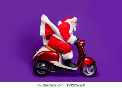 Photo of fat santa role man rushing newyear theme party by bike private presents courier wear sun specs and red x-mas costume isolated purple background