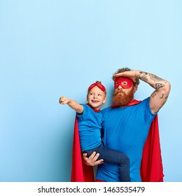 Photo of father and daughter play together, wear superhero costumes, happy small child on dads hands, pretends flying, look somewhere into distance, isolated on blue wall. Fathers day concept