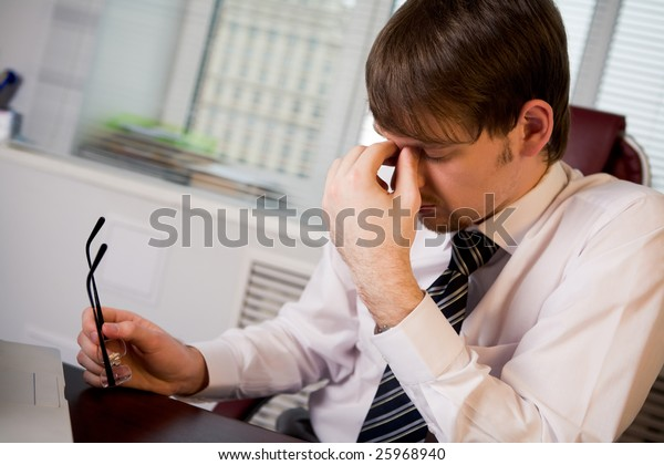 Photo of fatigue man with his eyeglasses off keeping his hand near face after hard working day