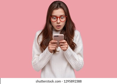 Photo of fearful dark haired lady stares at cell phone with surprised expression wears casual white sweater, reads shocking news on internet website, isolated over pink background. Astonishment