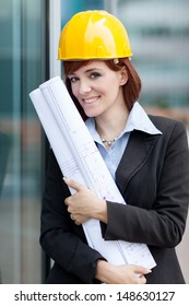 photo of female constructor with blueprints