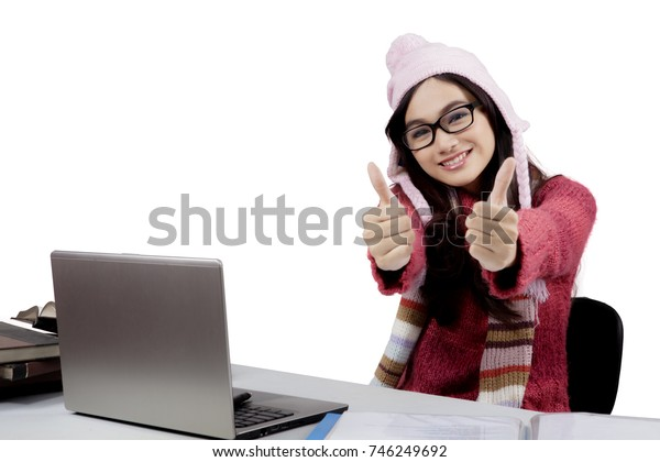 Photo of female college student wearing winter clothes and showing thumbs up at the camera while studying with a laptop