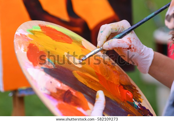 Photo of female hand artist who mixes oil or acrylic colored bright colors on wooden panel, which would start to draw and located in green park in open air. Concept of set of objects to paint, oil or