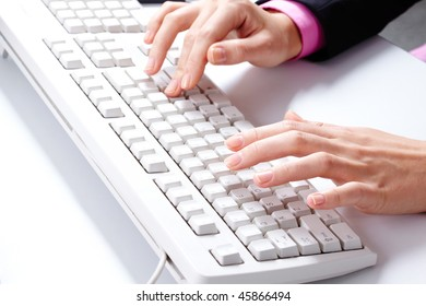 Photo of female hands over white keyboard pushing its buttons during work