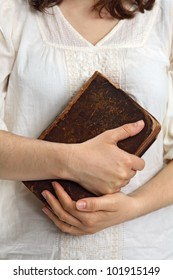 Photo of a female holding an old bible or book in her hands.