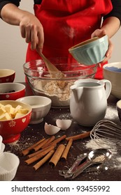Photo of a female mixing ingredients in a large glass bowl. Could be muffins, cookies, bread, etc.