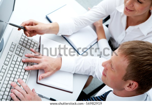 Photo of female pointing at monitor with typing man near by during discussion