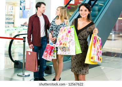 Photo of female standing with shopping bags in the trade centre on the background of young man and woman
