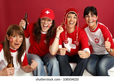 Photo of female Swiss sports fans smiling and cheering for their team.