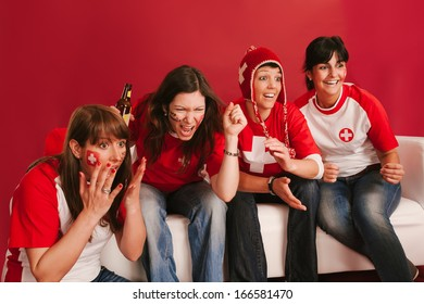 Photo of female Swiss sports fans watching television and cheering for their team.