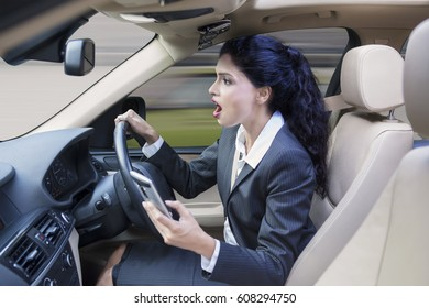 Photo of a female worker driving a car while using her smartphone and looks shocked at the road