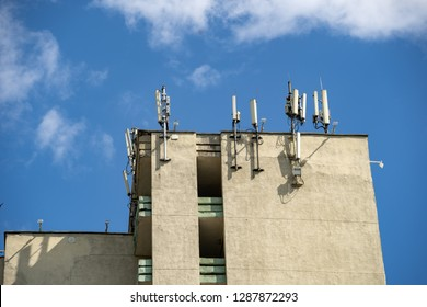 Photo of few single panel antennas of cellular systems on a steel mast at the roof of building