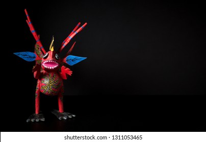 Photo of the figure of a mexican alebrije on a dark background.