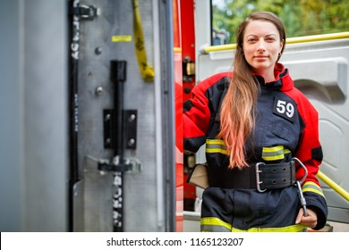 Photo of fire woman with long hair in overalls stands in fire engine