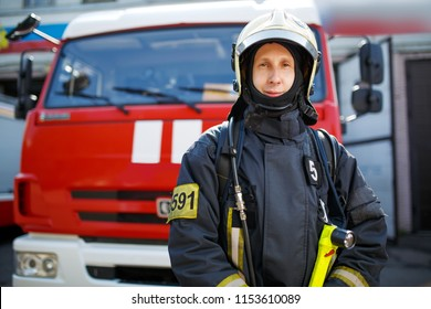 Photo of fireman in front of red car