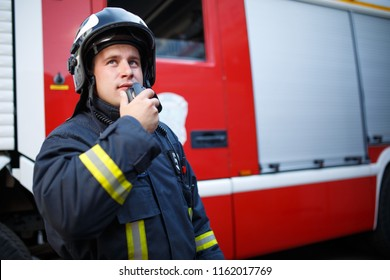 Photo of fireman talking on walkie-talkie with fire engine