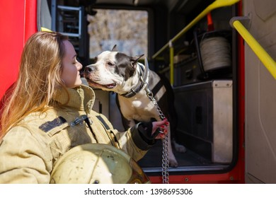 Photo of firewoman with dog standing near fire truck