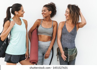 Photo of fitness multiethnic sportswomen in tracksuits smiling and standing over white wall outdoors