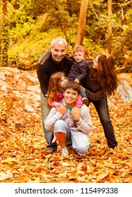 Photo of five happy person have fun outdoors, beautiful young parents play with two little children and adult son in autumnal backyard, happy family enjoying autumn nature, love concept