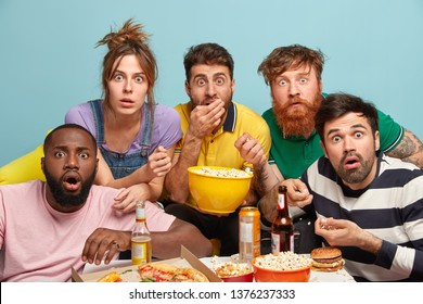 Photo of five mixed race woman and men watch thriller movie, horrible news, look in panic, eat popcorn, stare with bugged eyes, isolated over blue background, being scared. Scary film at home