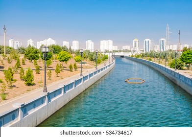 Photo of floating river surrounded by trees  with buldings in distance in Ashgabat in Turkmenistan.