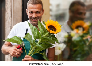 Photo of florist with a sunflower in his hands next to his shop