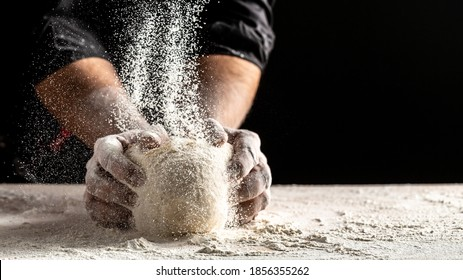 Photo of flour and men hands with flour splash. Cooking bread. Kneading the Dough. Isolated on dark background. Empty space for text.