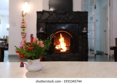 Photo of a flower vase in front of a fireplace