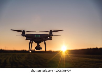 Photo of a flying white professional quadcopter drone camera during sunset