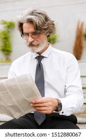 Photo of focused elderly businessman in eyeglasses reading newspaper while sitting outdoors