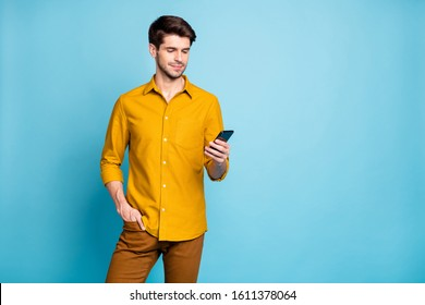 Photo of focused handsome bearded man wearing yellow shirt with hand in pocket holding telephone with hand reading feed news isolated over pastel color blue background