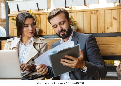Photo of focused office workers man and woman in formal wear looking at documents while using laptop and cellphone in cafe