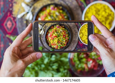 Photo of food in cafe with phone. Finger tap a screen to shoot a lunch in Arabic restaurant - tabbouleh with bulgur.