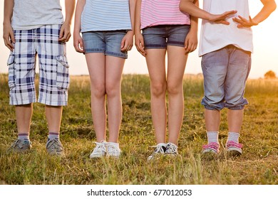 Photo of four kids legs standing at the summer sunny field, wearing casual summer clothes.