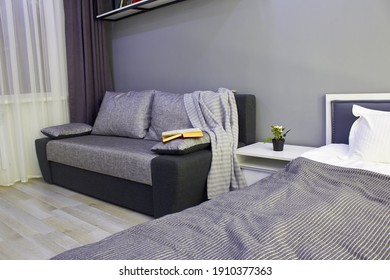 In the photo, a fragment of a beautiful modern bedroom in a room with a bed, sofa and other furniture.