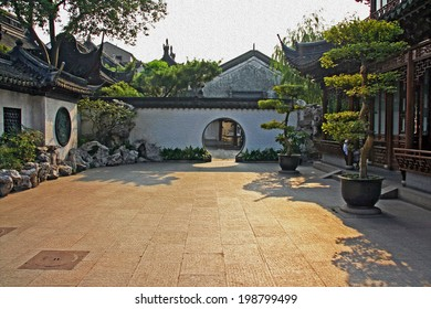 Photo of a fragment of  Yuyuan gardens, Shanghai with courtyard, bonsai trees and moon gates, stylized and filtered to resemble an oil painting.