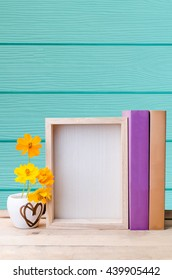 Photo frame, books and flowers on the wooden table with blue texture background