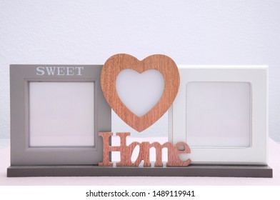 Photo frame with a closeup inscription heart on a light chest of drawers on a white background.
