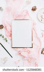 Photo frame with copy space on pink blanket with eucalyptus branches and rose flowers on white background. Flat lay, top view still life artist concept.