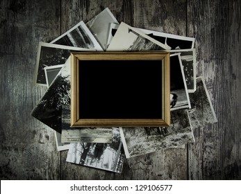Photo frame with lots of photos lying on an old table.