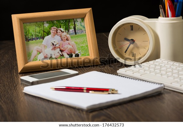 photo frame, mobile phone and notebook with a ballpoint pen. Workplace of the businessman.