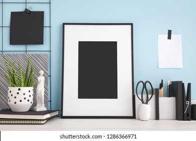 Photo frame mock up on a blue wall and home office supplies.