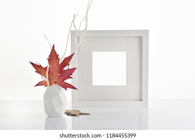 Photo frame mockup on table with decorative autumn vase
