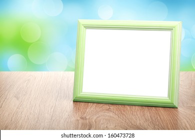 Photo frame on wood table over sunny day bokeh background