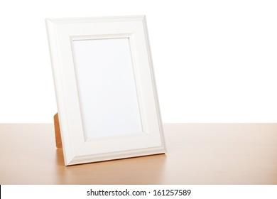 Photo frame on wood table. Isolated on white background