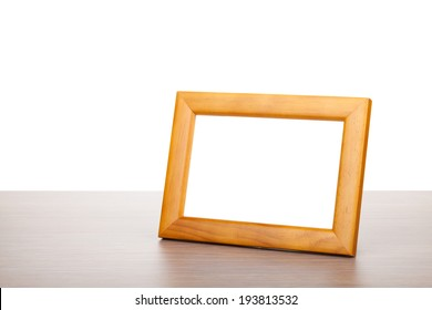 Photo frame on wooden table. Isolated on white background