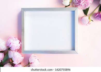 Photo frame with pink and white peony flowers with copy space for text on pink background. Flat lay, top view. Peony flower texture